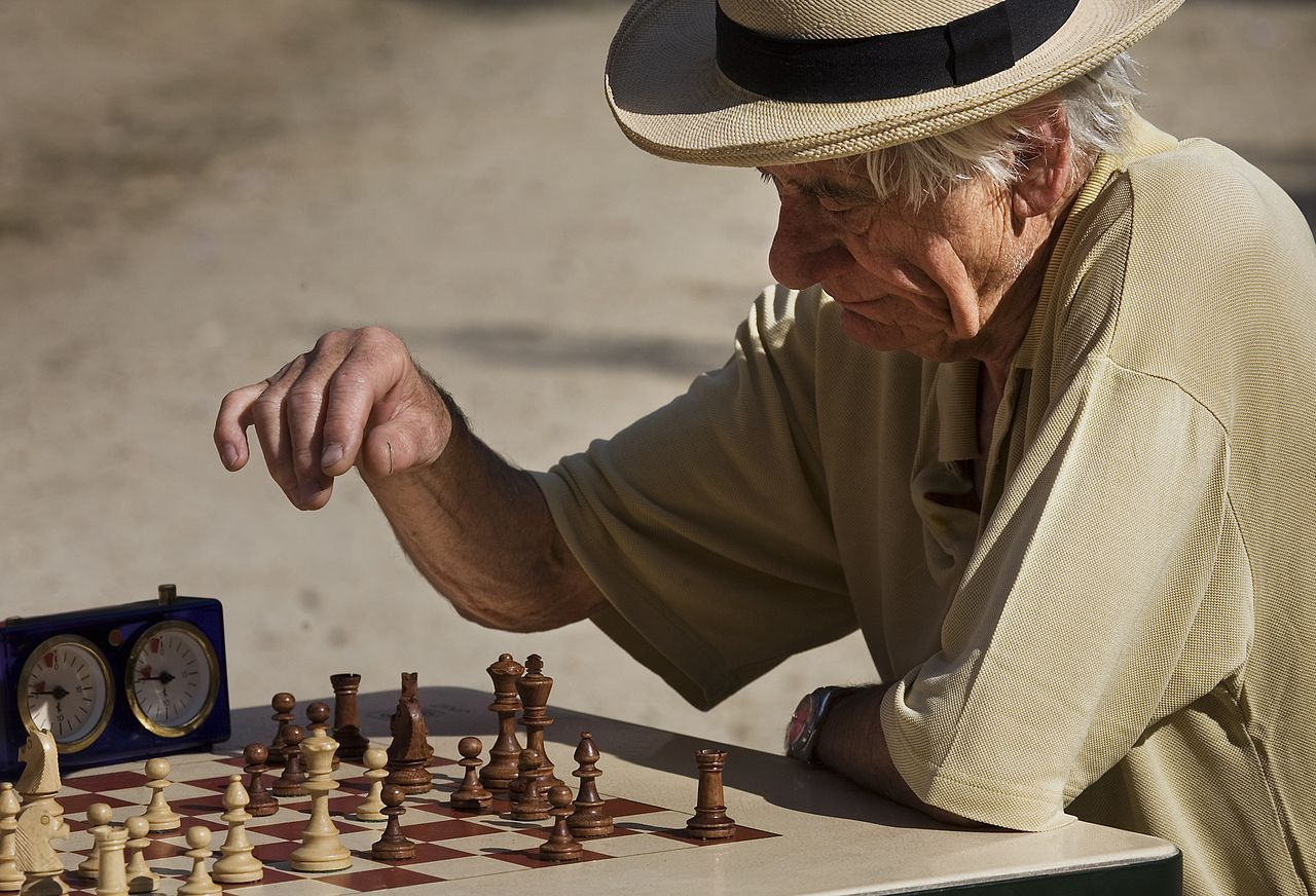 Old man playing timed chess